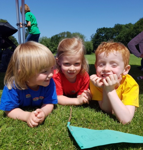 three kids relaxing on the grass